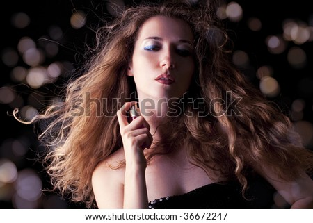 beautiful blond woman applying perfume on her body - stock photo