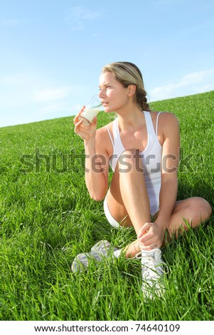 Beautiful blond woman drinking milk in countryside - stock photo