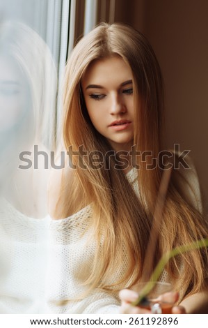 beautiful blond woman drinking tea in the morning sitting by the window - stock photo