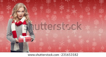 beautiful blond woman holding cristmas gift over winter snowflakes background - stock photo