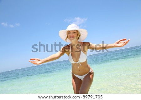 Beautiful blond woman in bikini by blue lagoon - stock photo