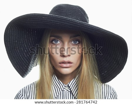 Beautiful Blond Woman in Black Hat. Fashionable model Elegance Beauty Girl.Young blonde with blue eyes - stock photo