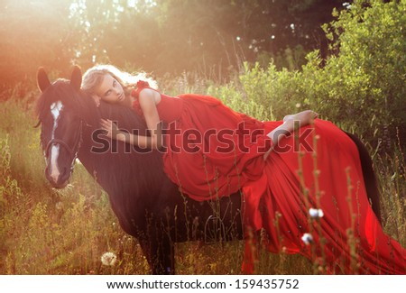 beautiful blond woman in red dress at black horse - stock photo