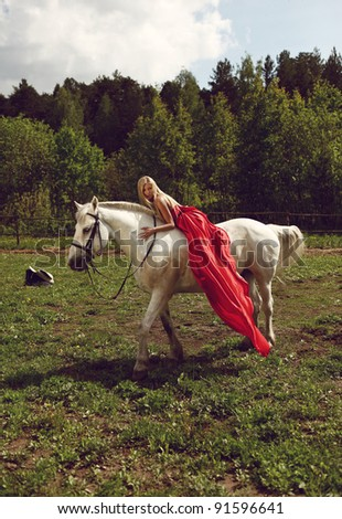 Beautiful blond woman in red dress on a white horse - stock photo