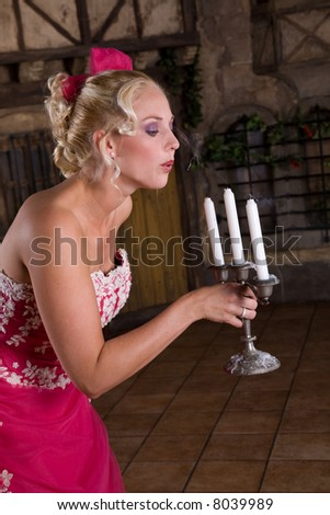Beautiful blond woman in wedding dress blowing out the candles - stock photo