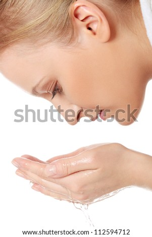Beautiful blond woman is cleaning her face - stock photo