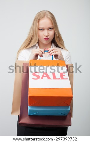 Beautiful blond woman is holding packets with things of sale. She is looking at the camera sadly. She is disappointed about her purchase. Isolated on background - stock photo