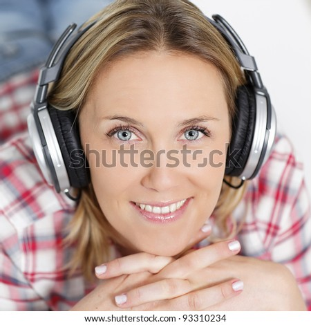 beautiful blond woman listening music with headphones - stock photo