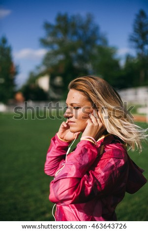 Beautiful blond woman listening to the music and working out.