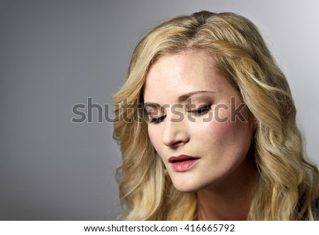 Beautiful blond woman looking down. Young, sad or thinking looking woman with copy space.