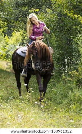 Beautiful blond woman on the brown horse. - stock photo