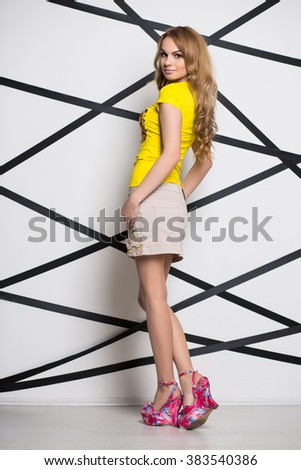 Beautiful blond woman posing in yellow t-shirt and beige skirt