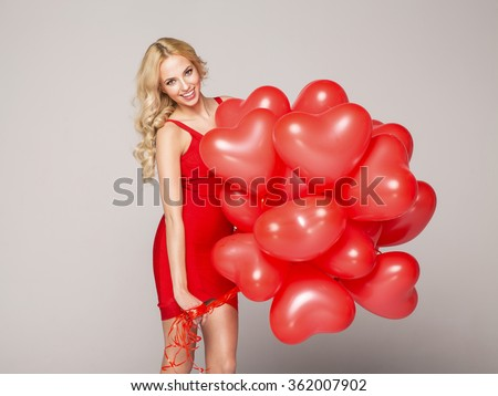 Beautiful blond woman posing on grey background in red dress, ho - stock photo
