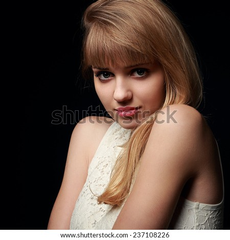 Beautiful blond woman posing with innocence look on black background. Closeup portrait - stock photo