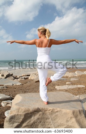 Beautiful blond woman practicing yoga at the beach