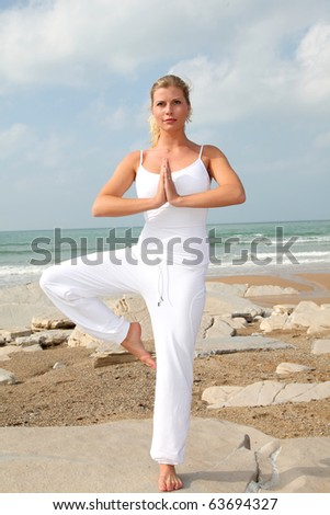 Beautiful blond woman practicing yoga at the beach - stock photo