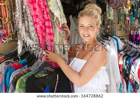 Beautiful blond woman shopping for accessories on holiday in greece. - stock photo