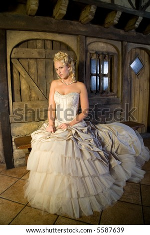 Beautiful blond woman sitting in serene pose on a bench in front of a fairytale house - stock photo