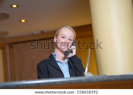 Beautiful blond woman wearing a suit answering an office telephone at work