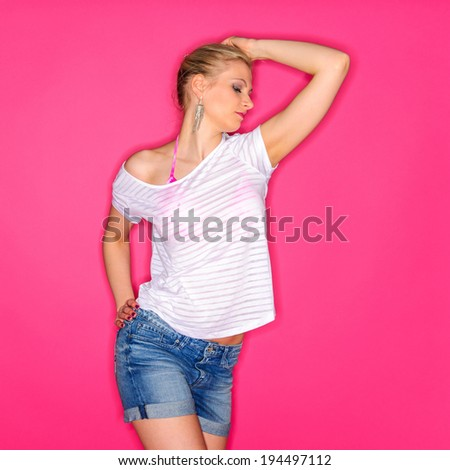 Beautiful blond woman wearing a white shirt and a denim shorts and posing against a pink studio background - stock photo