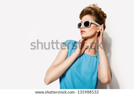 Beautiful blond woman wearing blue and brown dress and glasses - stock photo