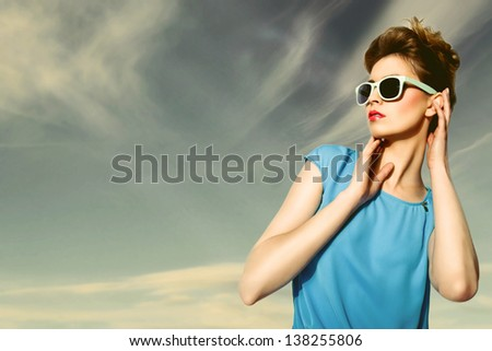 Beautiful blond woman wearing blue and brown dress and glasses. Retro style - stock photo