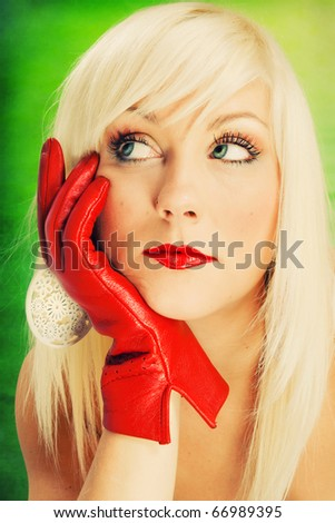 Beautiful blond woman wearing red gloves on a green background - stock photo