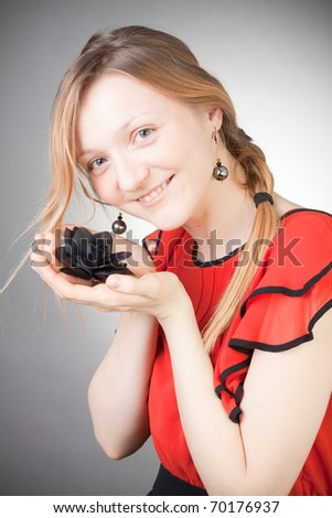 Beautiful blond woman wears red dress, smells black flower, with grey background - stock photo