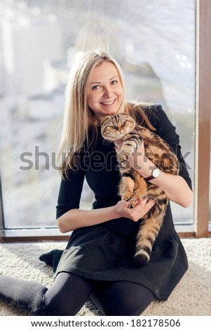 Beautiful blond woman with a cat - stock photo