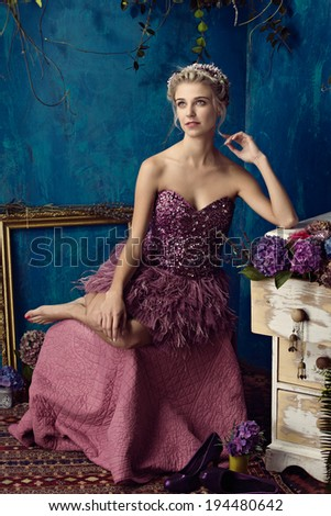 Beautiful blond woman with braid hairstyle and natural makeup. Wearing pink bohemian sequin and feather dress. Against blue grunge background - stock photo