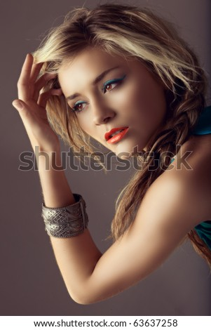beautiful blond woman with braided hair and coral lipstick in retro cross-process effect - stock photo