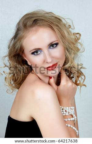 beautiful blond woman with curly hair and dark evening make-up wearing corset and pearls . - stock photo