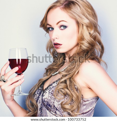 Beautiful blond woman with glass red wine - stock photo