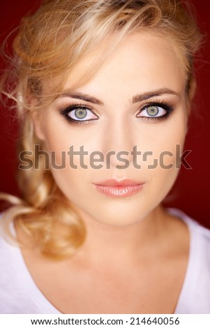 Beautiful blond woman with grey blue eyes wearing eye makeup looking directly into the camera with a serious expression - stock photo