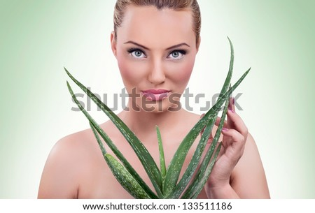 Beautiful blond woman with healthy skin  and aloe - stock photo