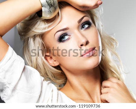 Beautiful blond woman with long curly hair and style makeup. Girl posing in studio