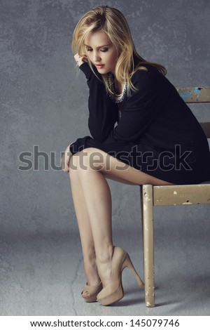 Beautiful blond woman with long legs wearing black cardigan, beige high heels on grunge studio background sitting on a rustic chair - stock photo