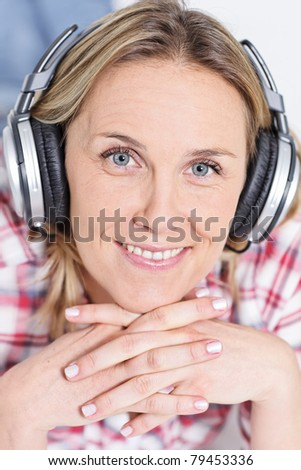 beautiful blond womanlistening music with headphones - stock photo
