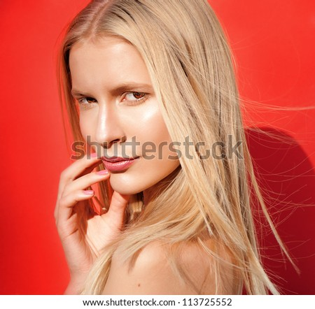 beautiful blond women pink lips looking on red background - stock photo