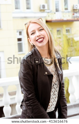 Beautiful blond young hipster girl with red lipstick and bright makeup on a sunny day outdoors. Smiling sexy woman dressed in a black leather jacket posing near old buildings in France, Italy, Spain.