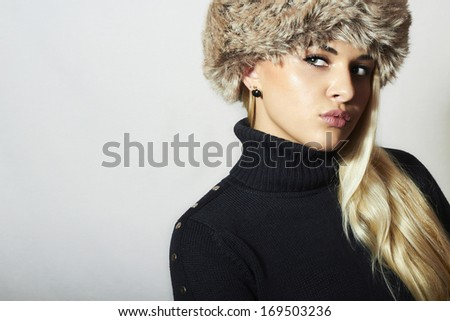Beautiful Blond Young Woman in Fur Hat. Beauty Fashion Girl. Winter Style. Green Eyes. Make-up. Golden Apple - stock photo
