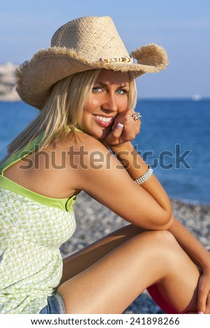 Beautiful blond young woman or girl in her twenties happy smiling wearing straw cowboy hat sitting on a beach with blue sea - stock photo