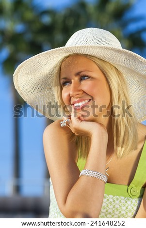 Beautiful blond young woman or girl in her twenties happy smiling wearing sun hat resting on her hand in sunshine on summer day with blue sky and palm trees - stock photo
