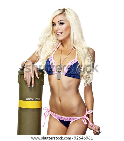 Beautiful blond young woman wearing pink and blue bikini next to explosive bomb. - stock photo