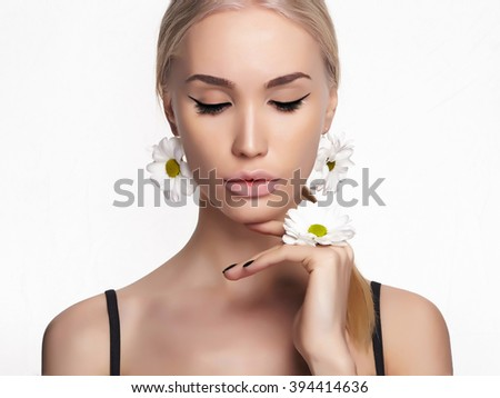beautiful blond young woman with chamomile accessories. beauty spring girl with flowers