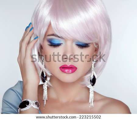 Beautiful blond young woman with fashion earring. Makeup. Manicured nails. Studio photo. Girl with Short Hair - stock photo