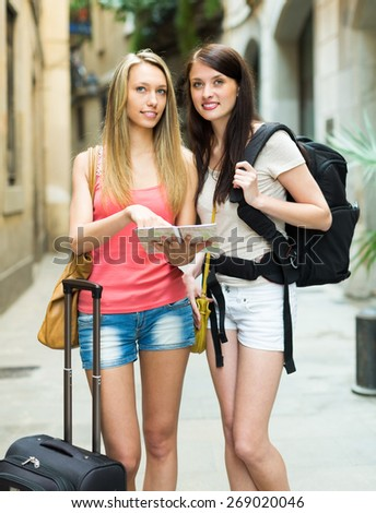 Beautiful blonde and brunette with luggage standing at the street  with map - stock photo