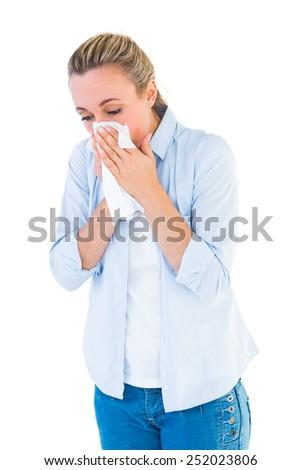 Beautiful blonde blowing nose on tissue on white bakcground - stock photo