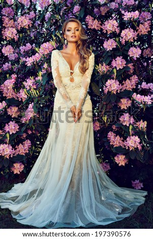 beautiful blonde bride in a luxurious wedding dress in garden with blossom - stock photo
