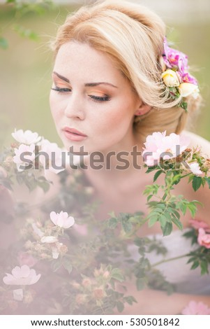 Beautiful Blonde Bride in White Dress with Flowers in her hairstyle